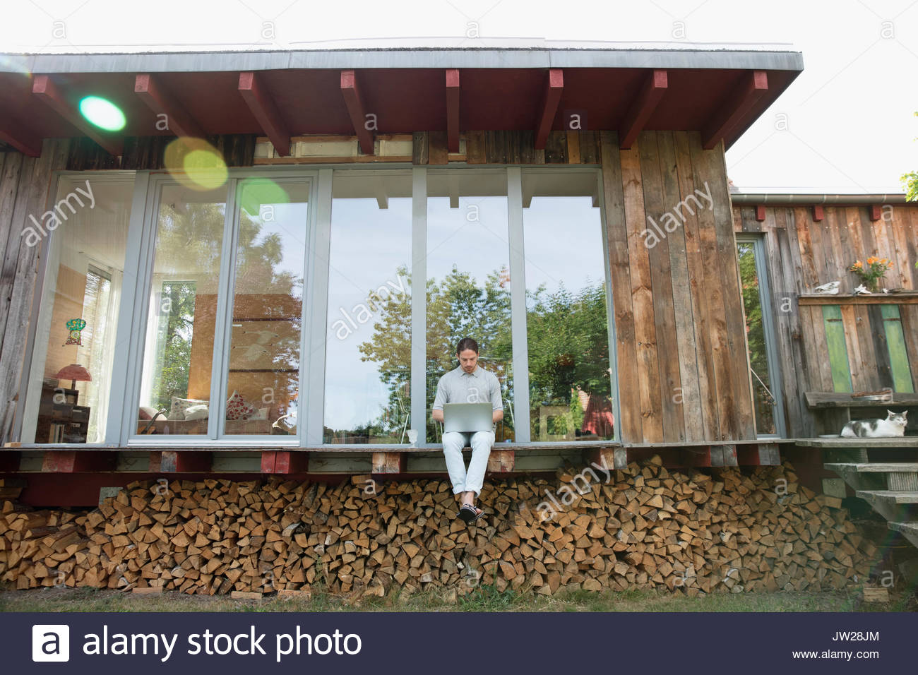 Young man using laptop on wood cabin patio above firewood - Stock Image