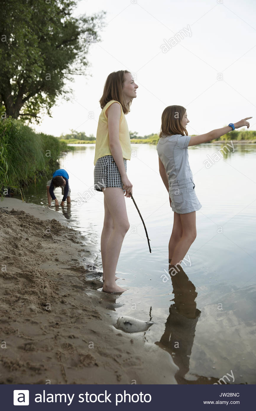 Curious girls pointing in summer lake - Stock Image
