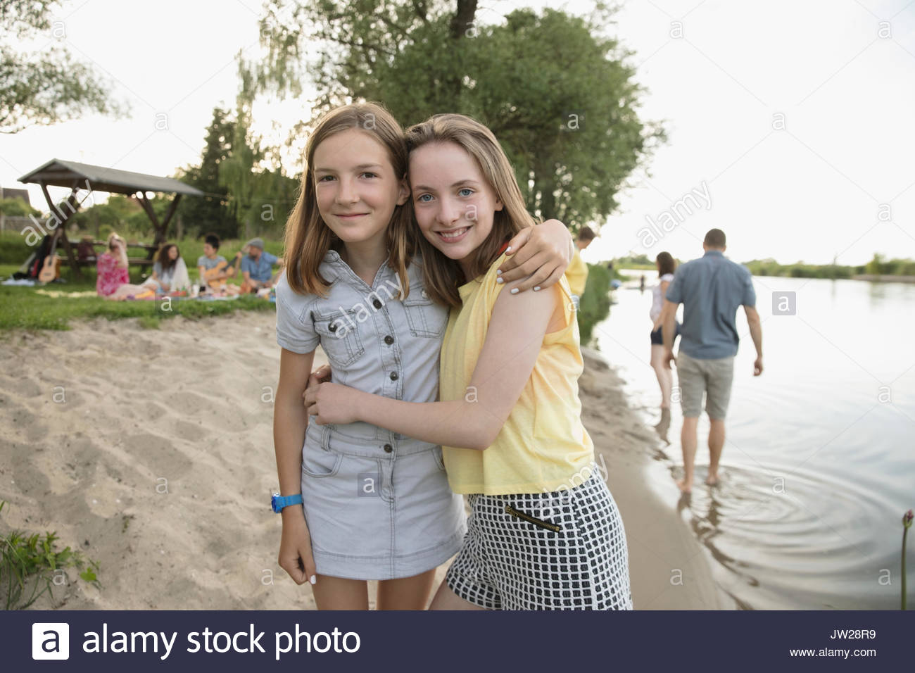 Portrait smiling pre-adolescent sisters hugging on summer lakeside beach - Stock Image