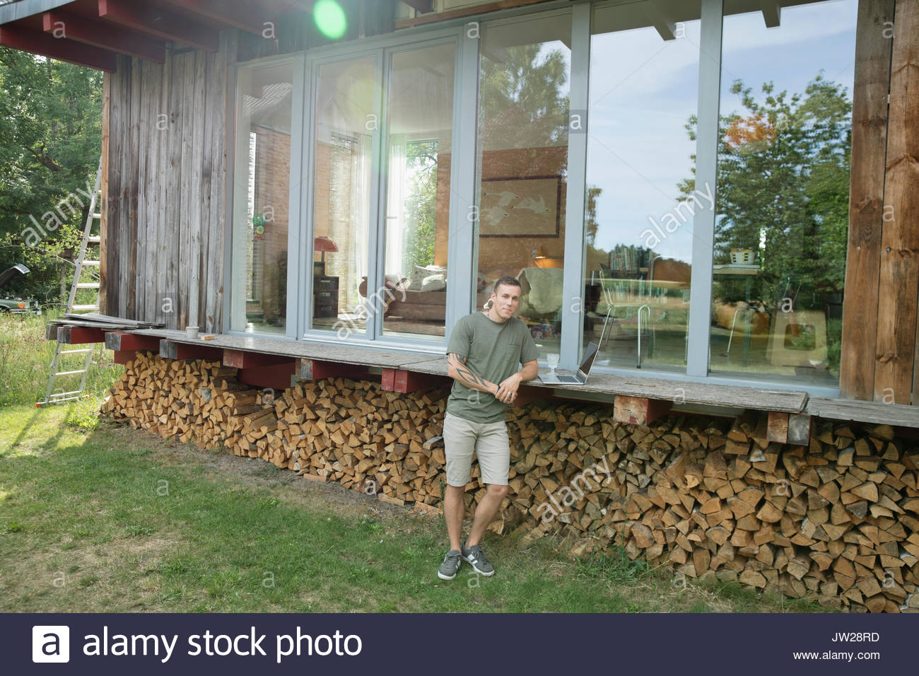 Portrait young man with laptop on wood cabin patio above firewood - Stock Image