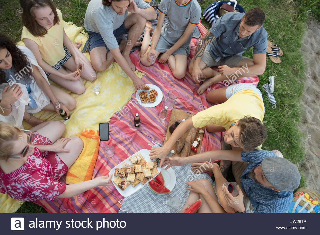 Overhead view friends and family enjoying summer picnic - Stock Image