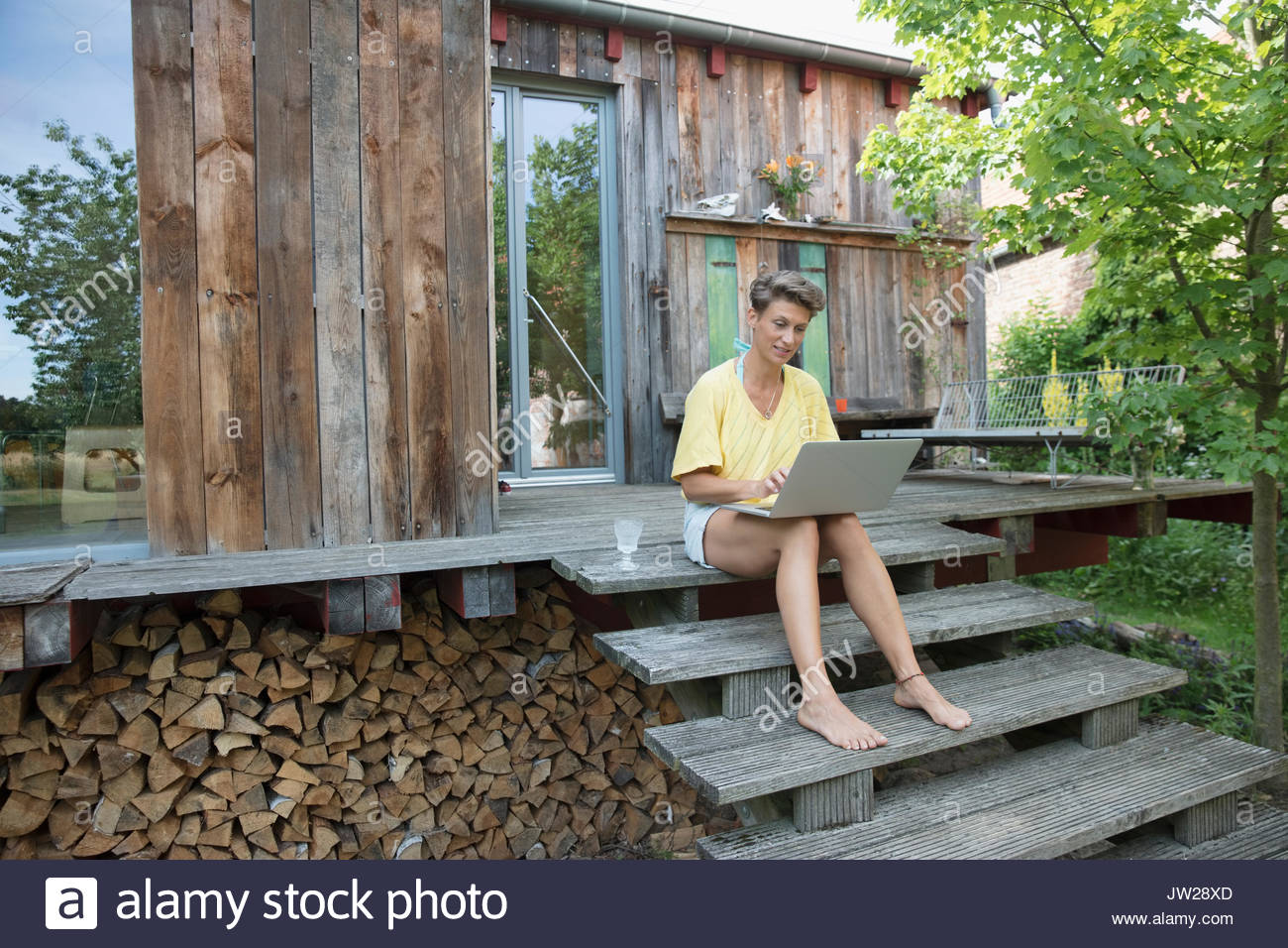 Barefoot woman using laptop on wood cabin steps - Stock Image
