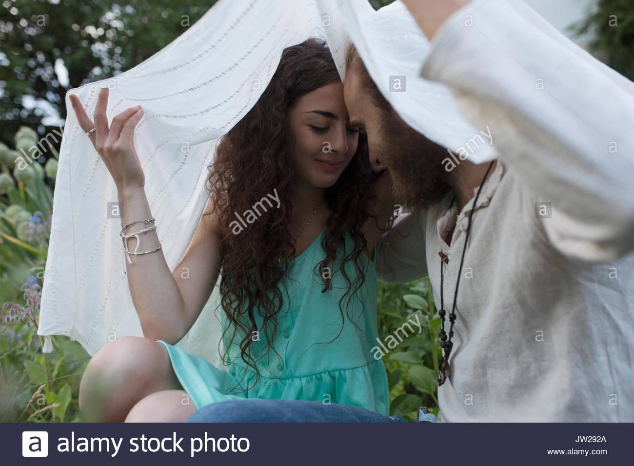 Affectionate, serene couple under shawl - Stock Image