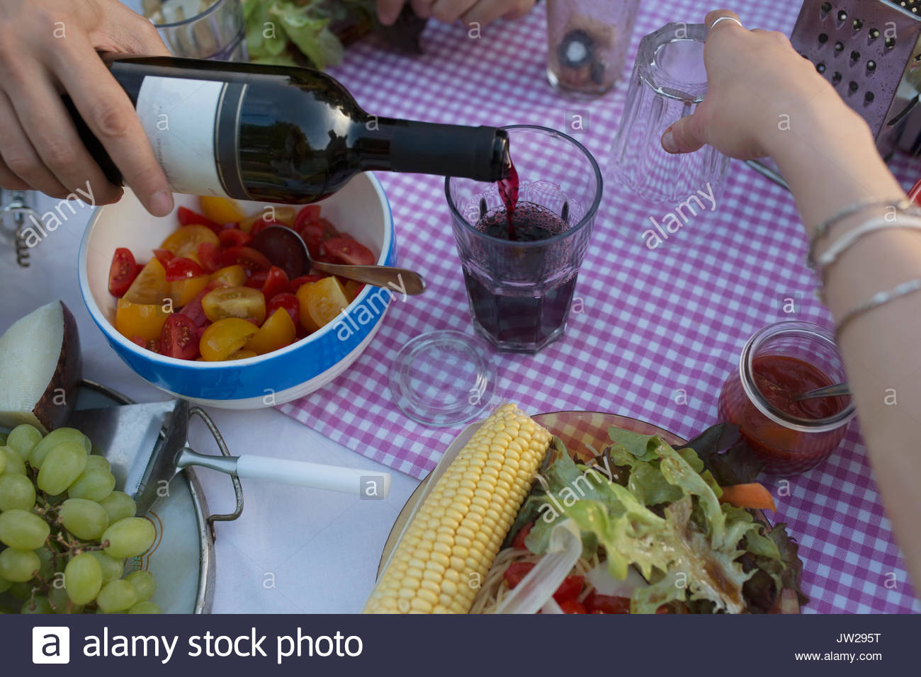 Man pouring red wine at dinner table - Stock Image