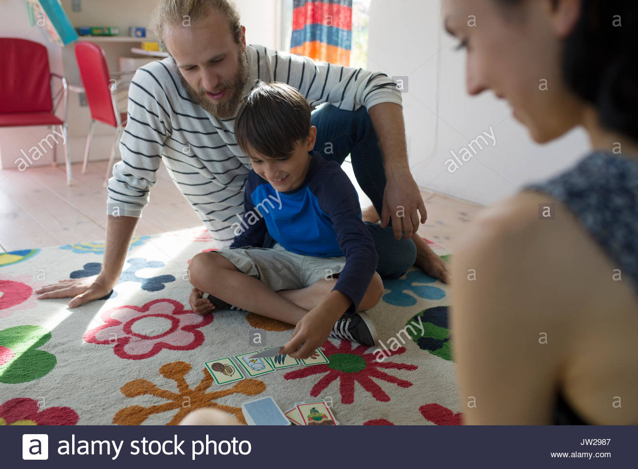 Family playing card game on pattern rug - Stock Image