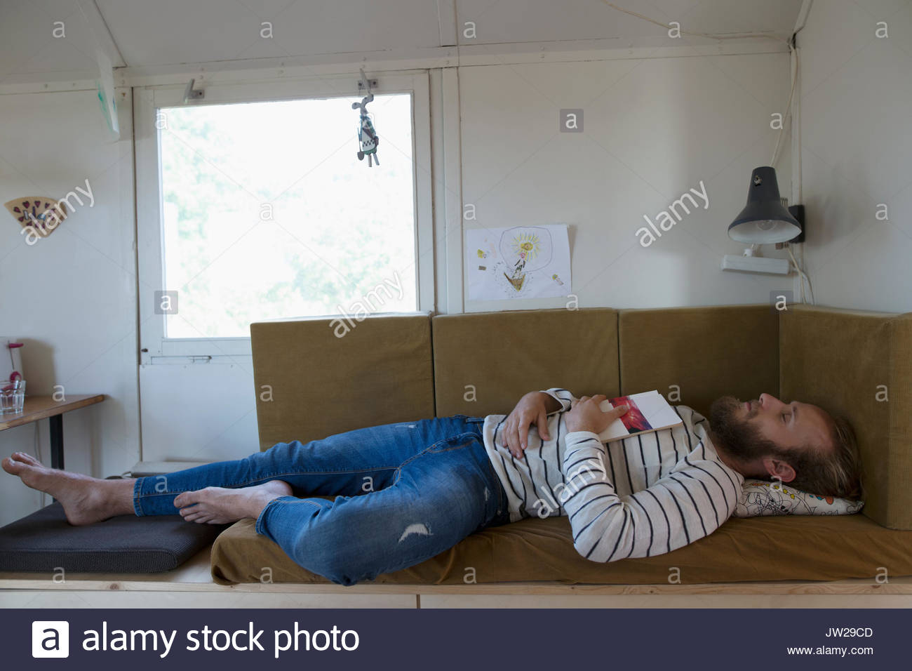 Tired, serene man with book sleeping on caravan bench - Stock Image