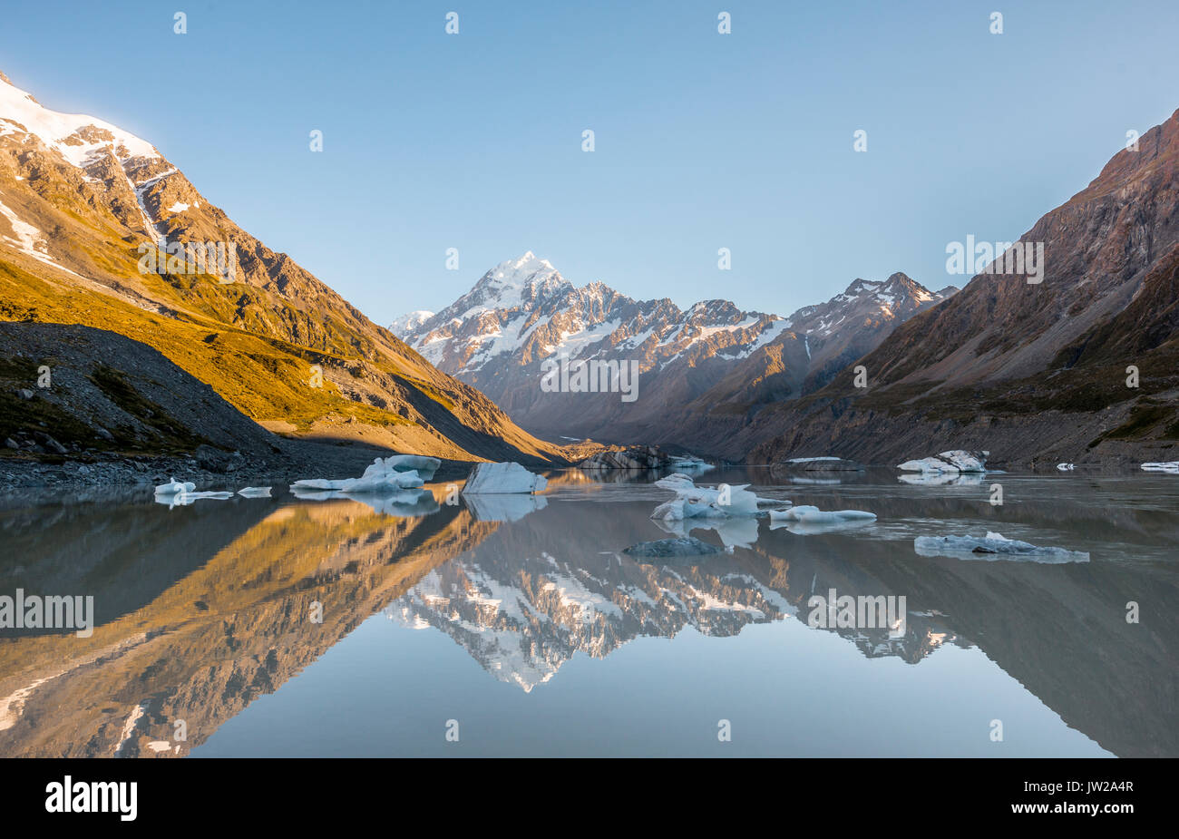 Sunrise, reflection in Hooker Lake, morning sun illuminating Mount Cook, Mount Cook National Park, Southern Alps, Hooker Valley - Stock Image