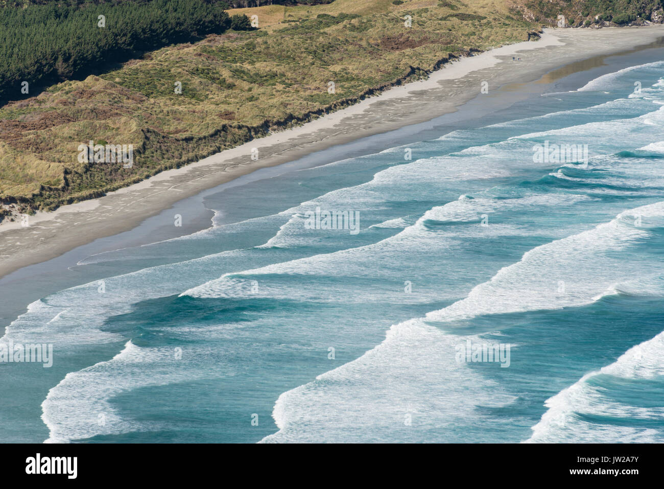 Spinning waves breaking at the flat sand beach, Allans Beach, Dunedin, Otago Peninsula, South Island, New Zealand - Stock Image