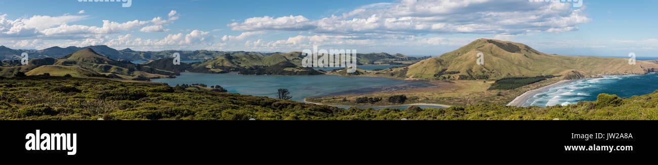 Hoopers Inlet, green hilly landscape between ocean and pacific ocean, Dunedin, Otago Peninsula, South Island, New Zealand - Stock Image