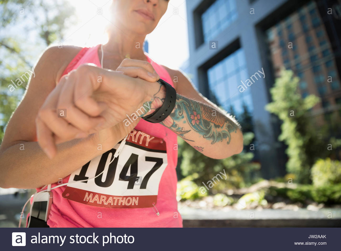 Tattooed female marathon runner checking smart watch in urban park - Stock Image