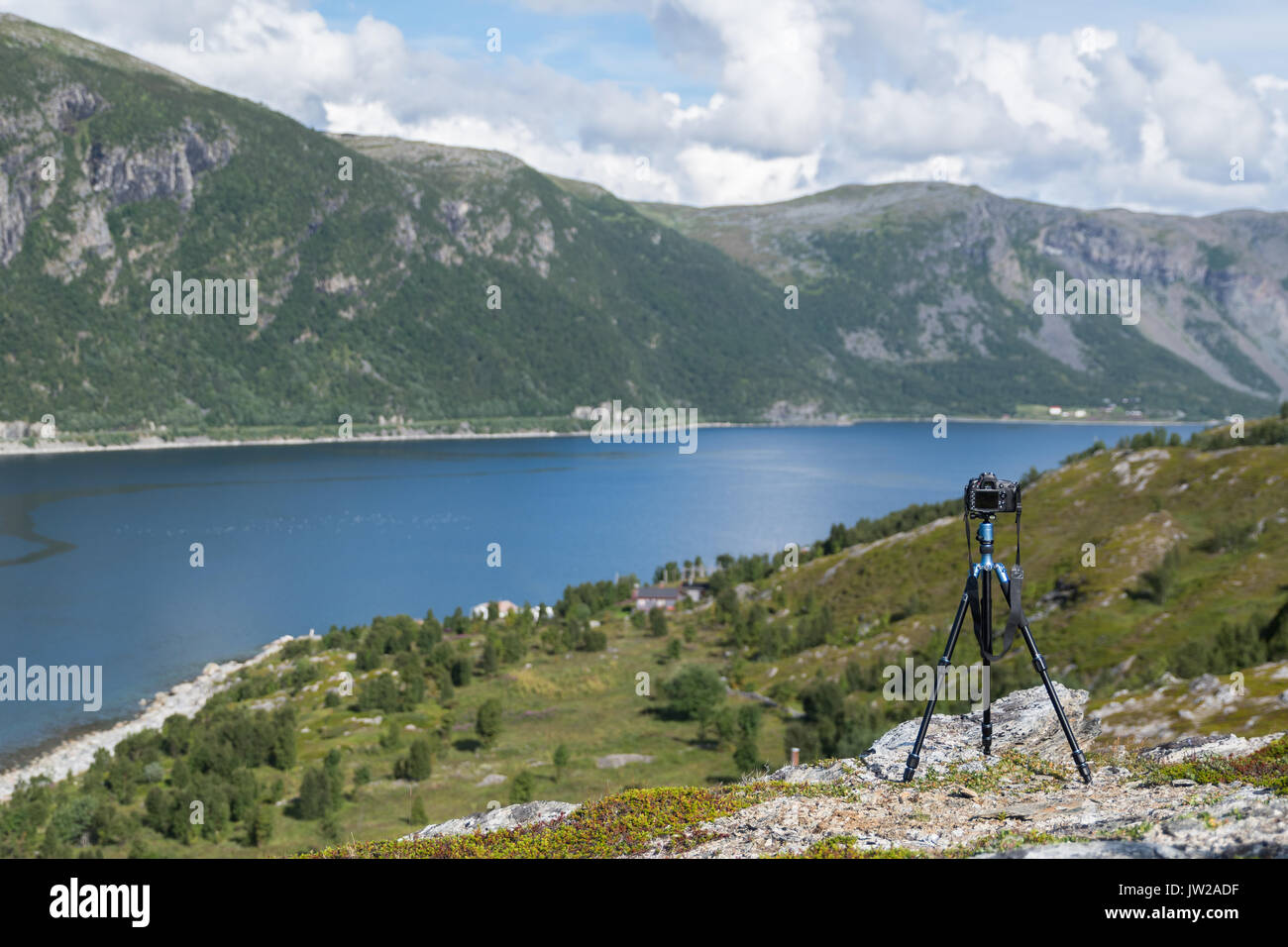 Black camera on tripod taking time lapse pictures - Stock Image
