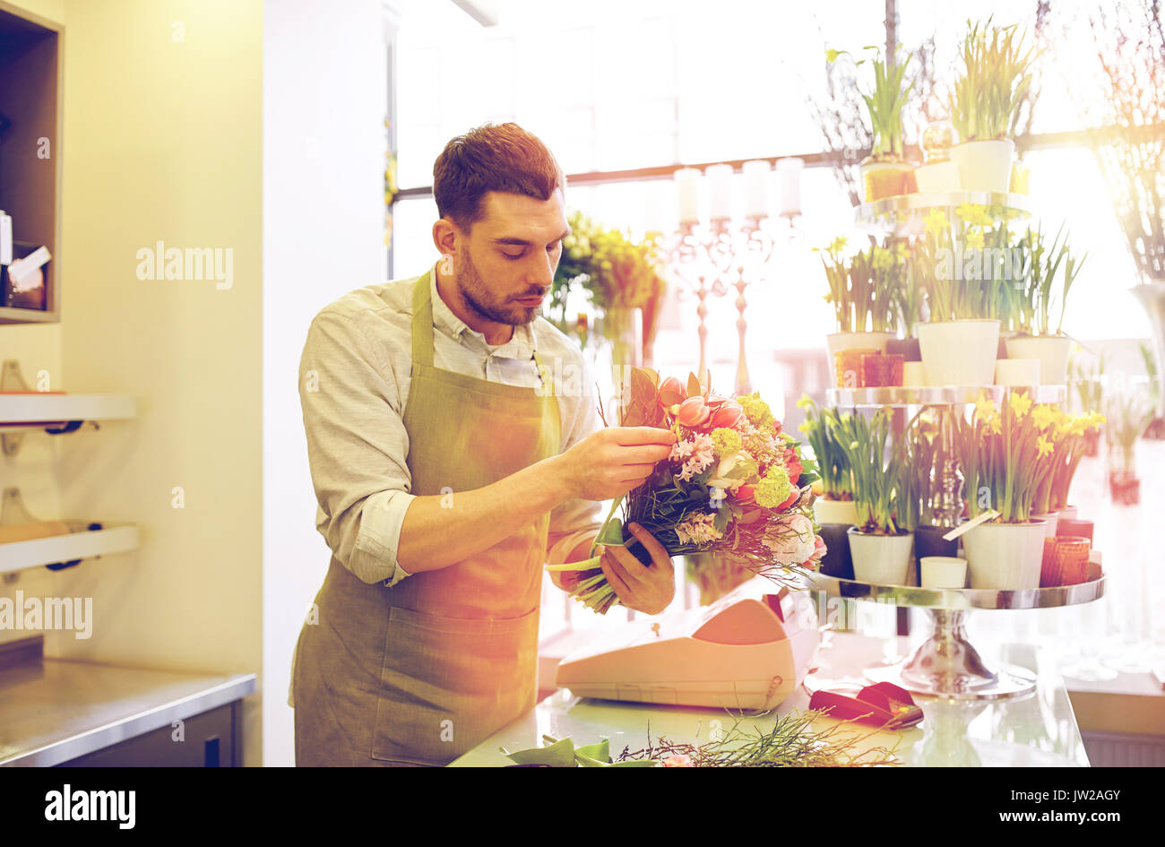 florist man making bunch at flower shop - Stock Image
