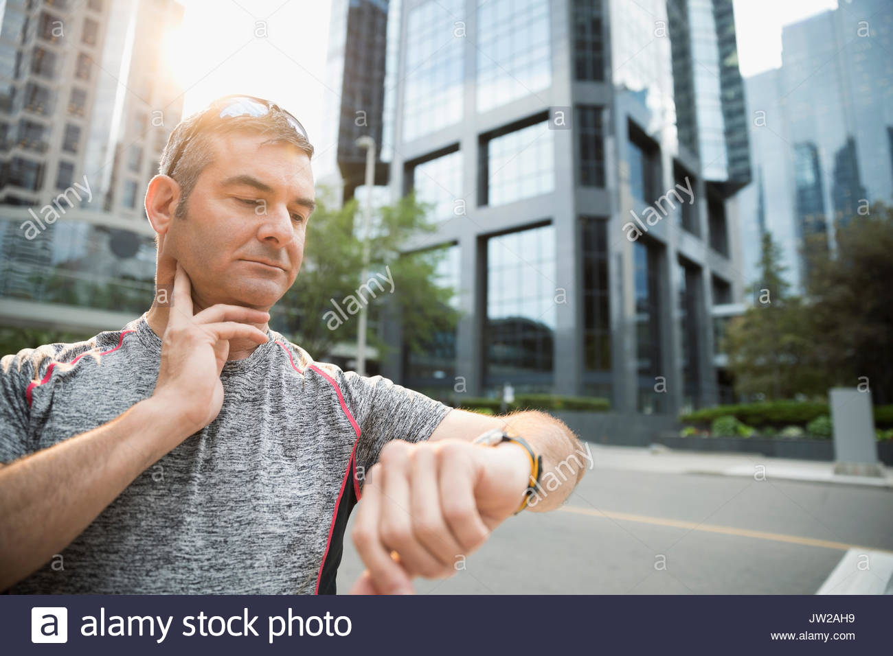 Male runner checking pulse with smart watch on urban street - Stock Image