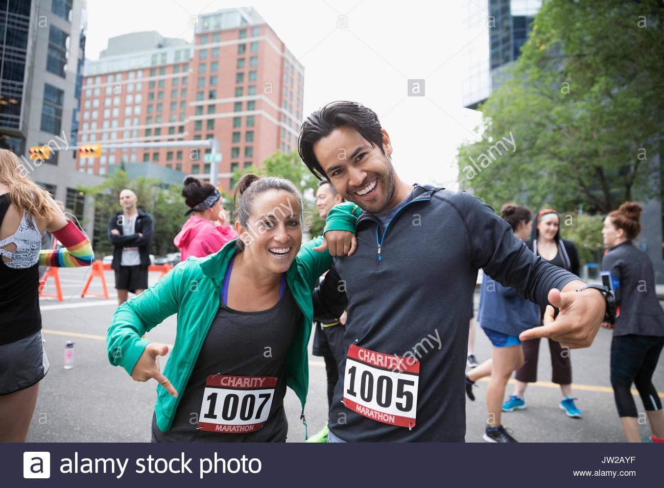 Portrait enthusiastic couple pointing to marathon bibs on urban street - Stock Image