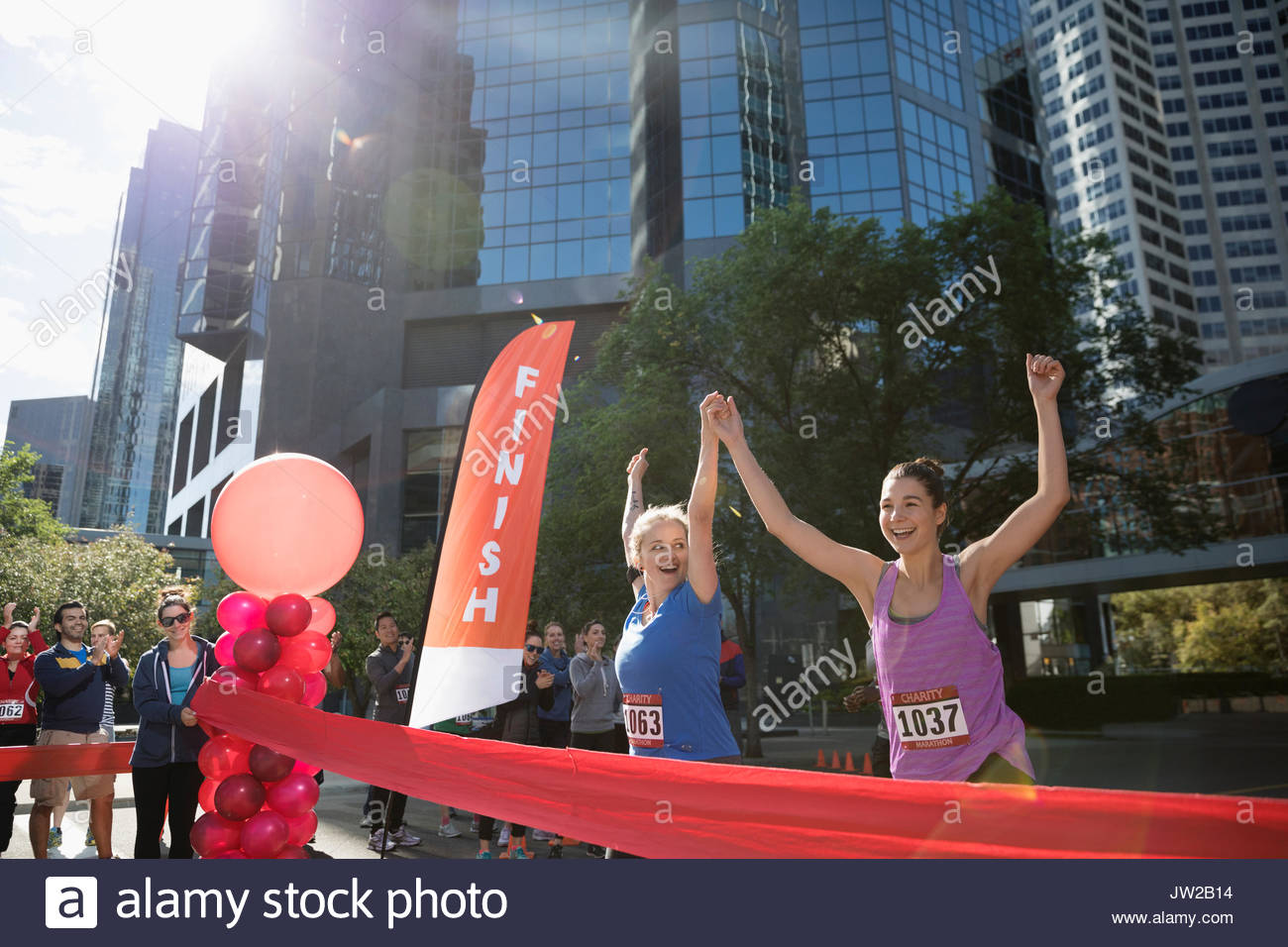 Exuberant female marathon runners holding hands crossing finish line with arms raised - Stock Image