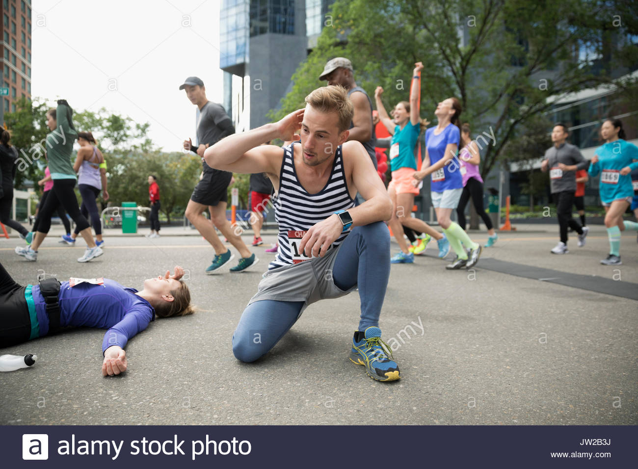 Exhausted marathon runners collapsing at finish line - Stock Image