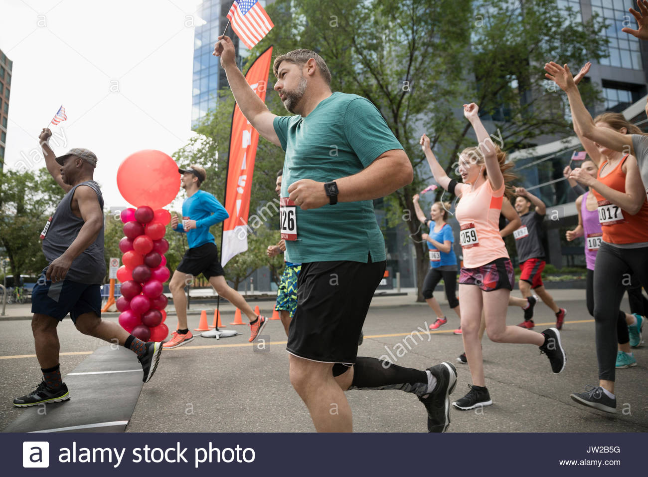 Marathon runners with American flags crossing finish line - Stock Image