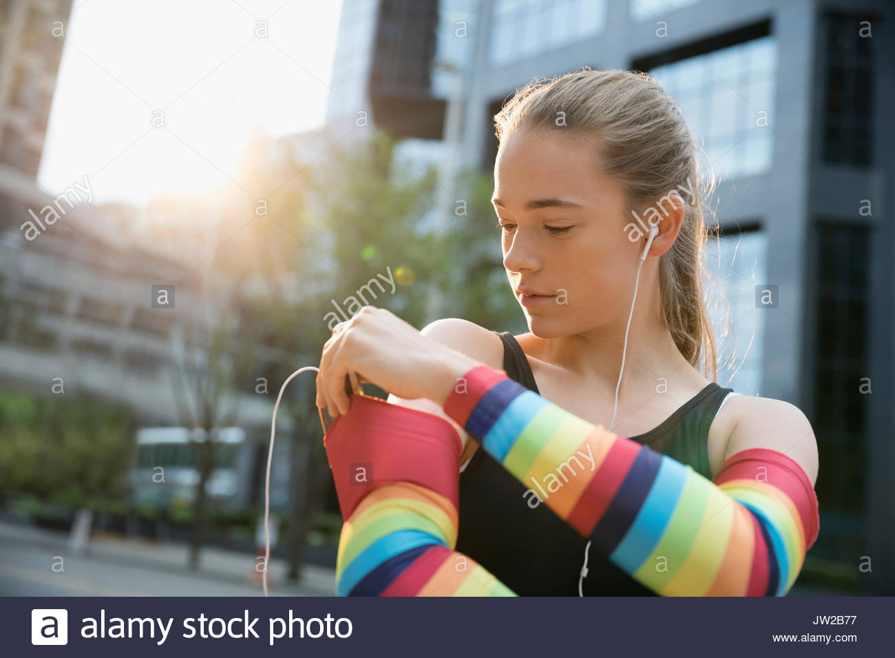 Teenage girl runner wearing rainbow compression arm sleeves, listening to music with mp3 player and earbud headphones - Stock Image
