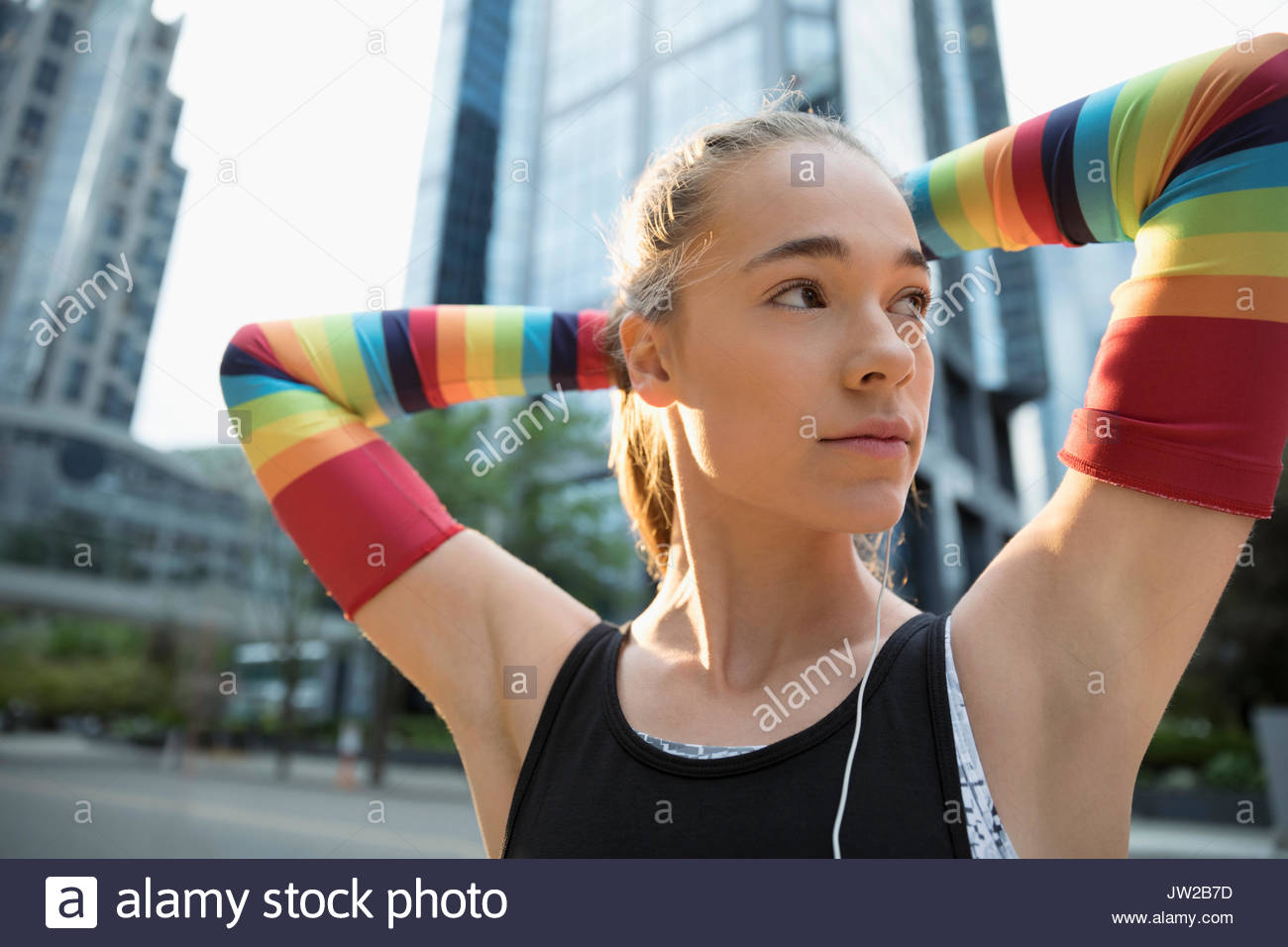 Teenage girl runner wearing rainbow compression arm sleeves with hands behind head - Stock Image