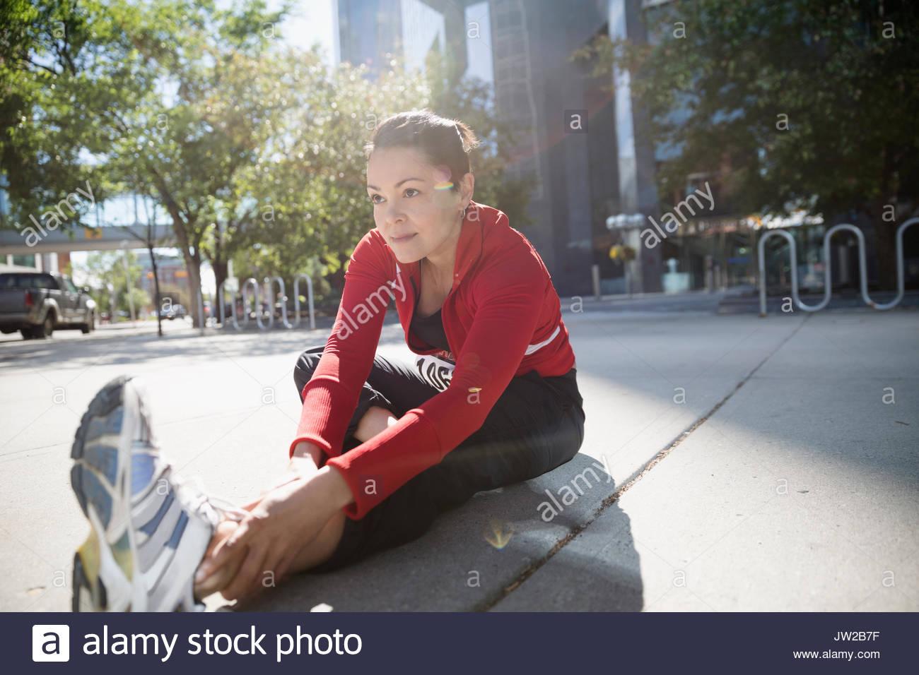 Woman stretching leg on sunny urban sidewalk - Stock Image