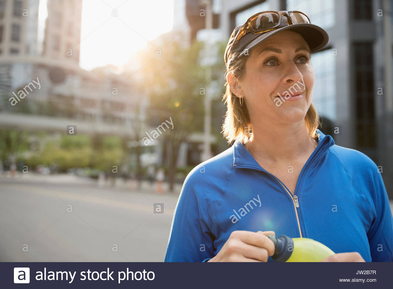 Mature female runner with water bottle on urban street - Stock Image