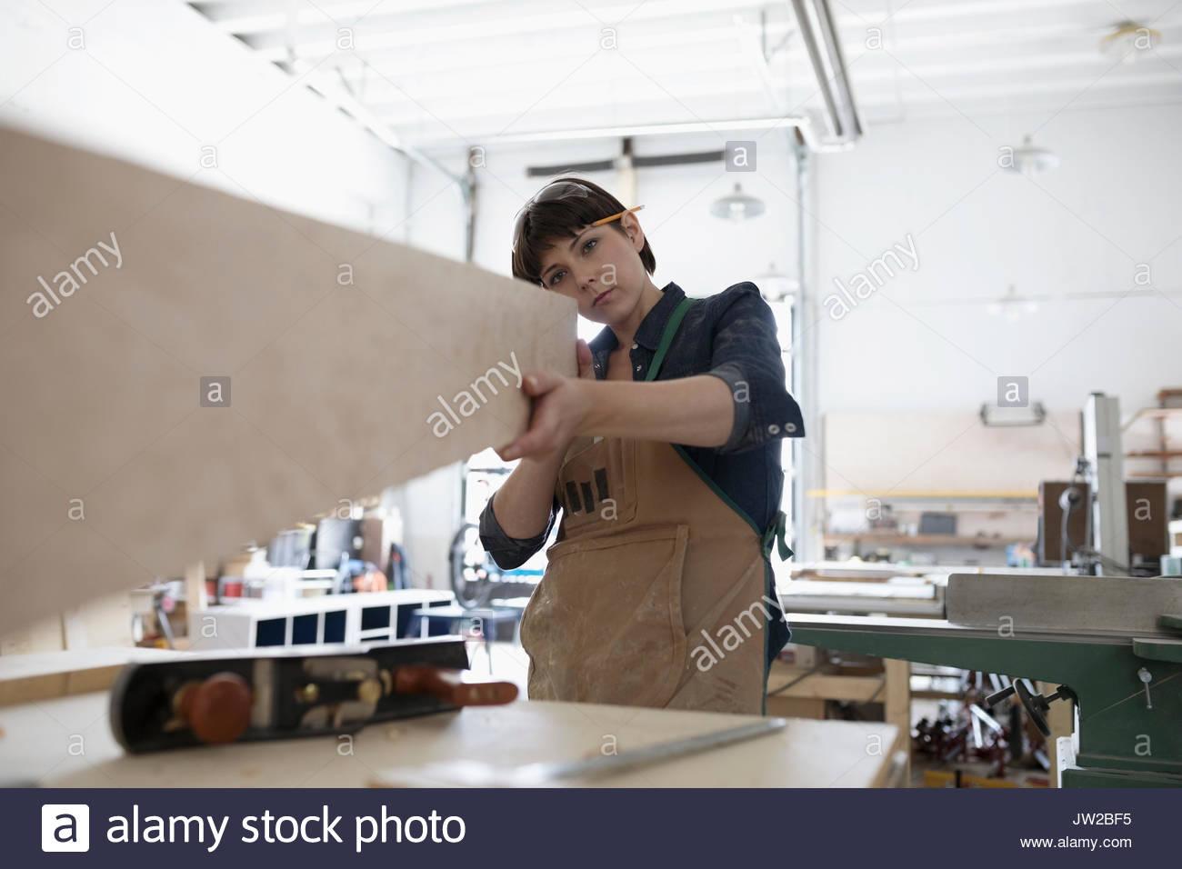 Focused female carpenter examining wood block in workshop - Stock Image
