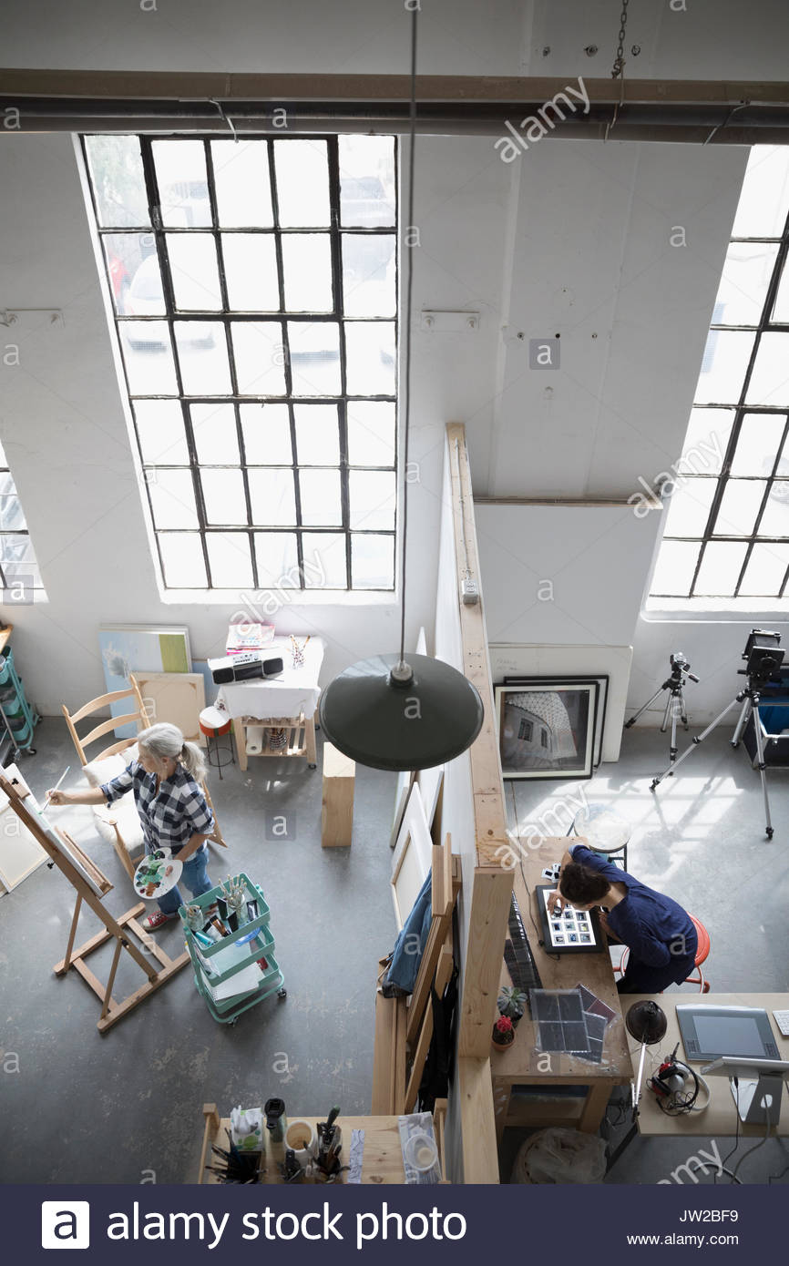 Female painter painting at canvas and photographer reviewing photographic slides in coworking space art studio - Stock Image