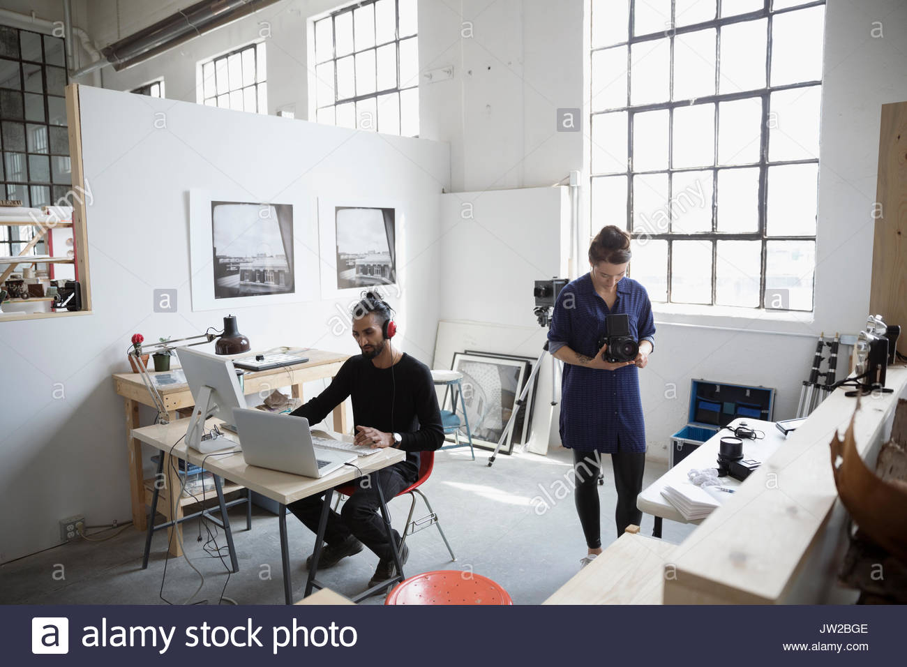 Photographers working at laptop and with digital camera in art studio - Stock Image