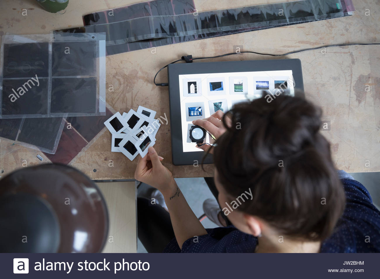 View from above female photographer reviewing photographic slides with lens magnifying loupe in art studio - Stock Image