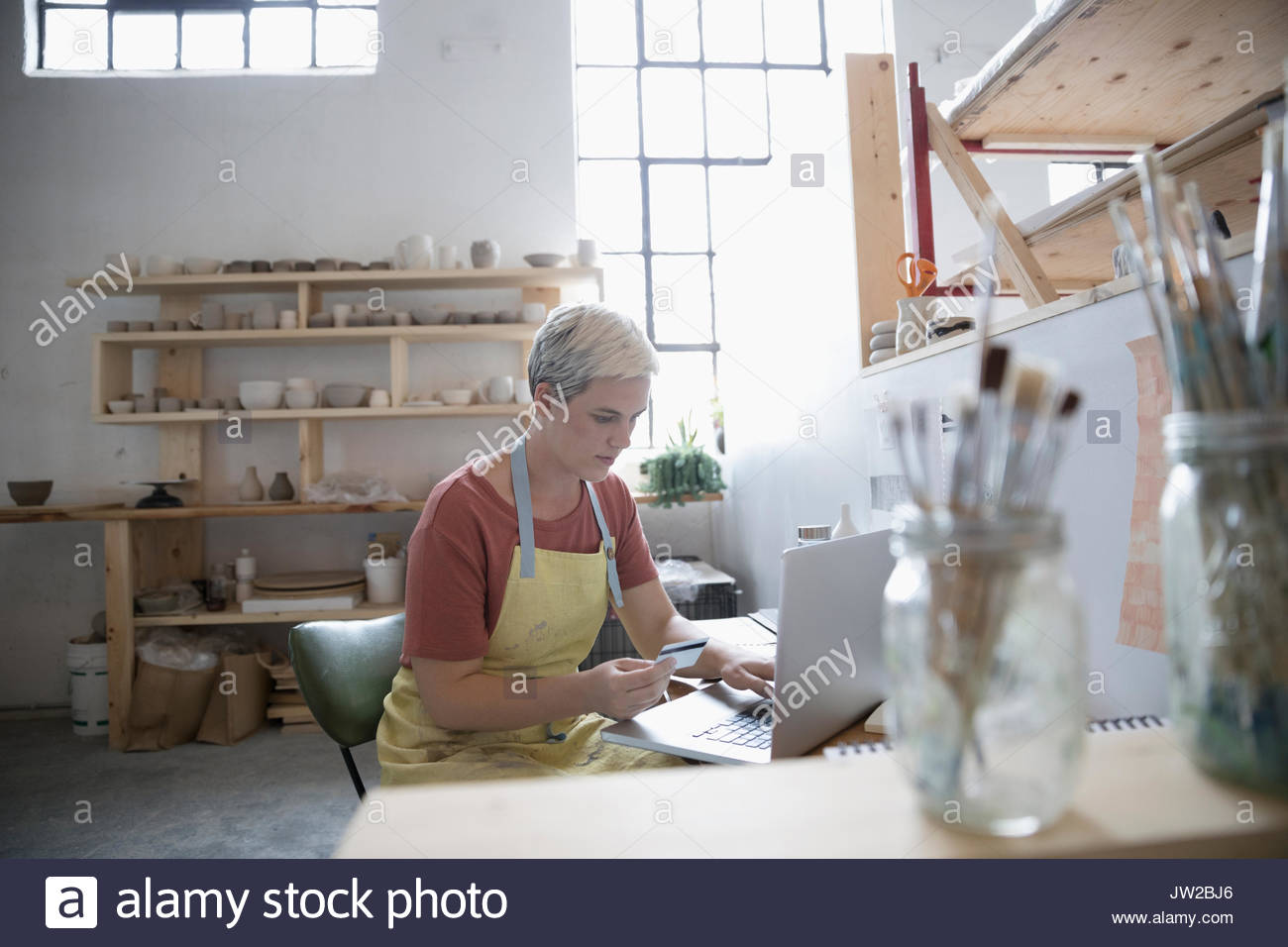 Female potter online shopping, ordering supplies with credit card at laptop in art studio - Stock Image