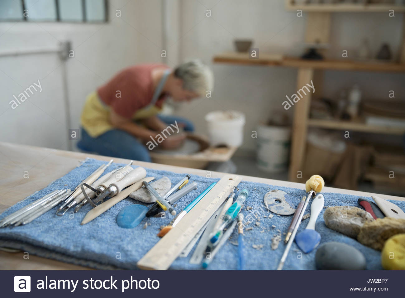 Female potter using pottery wheel behind tools on workbench in art studio - Stock Image