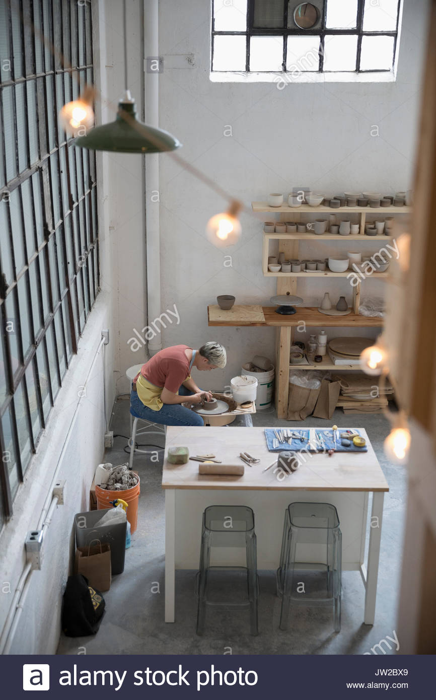 Elevated view female pottery using pottery wheel in art studio - Stock Image