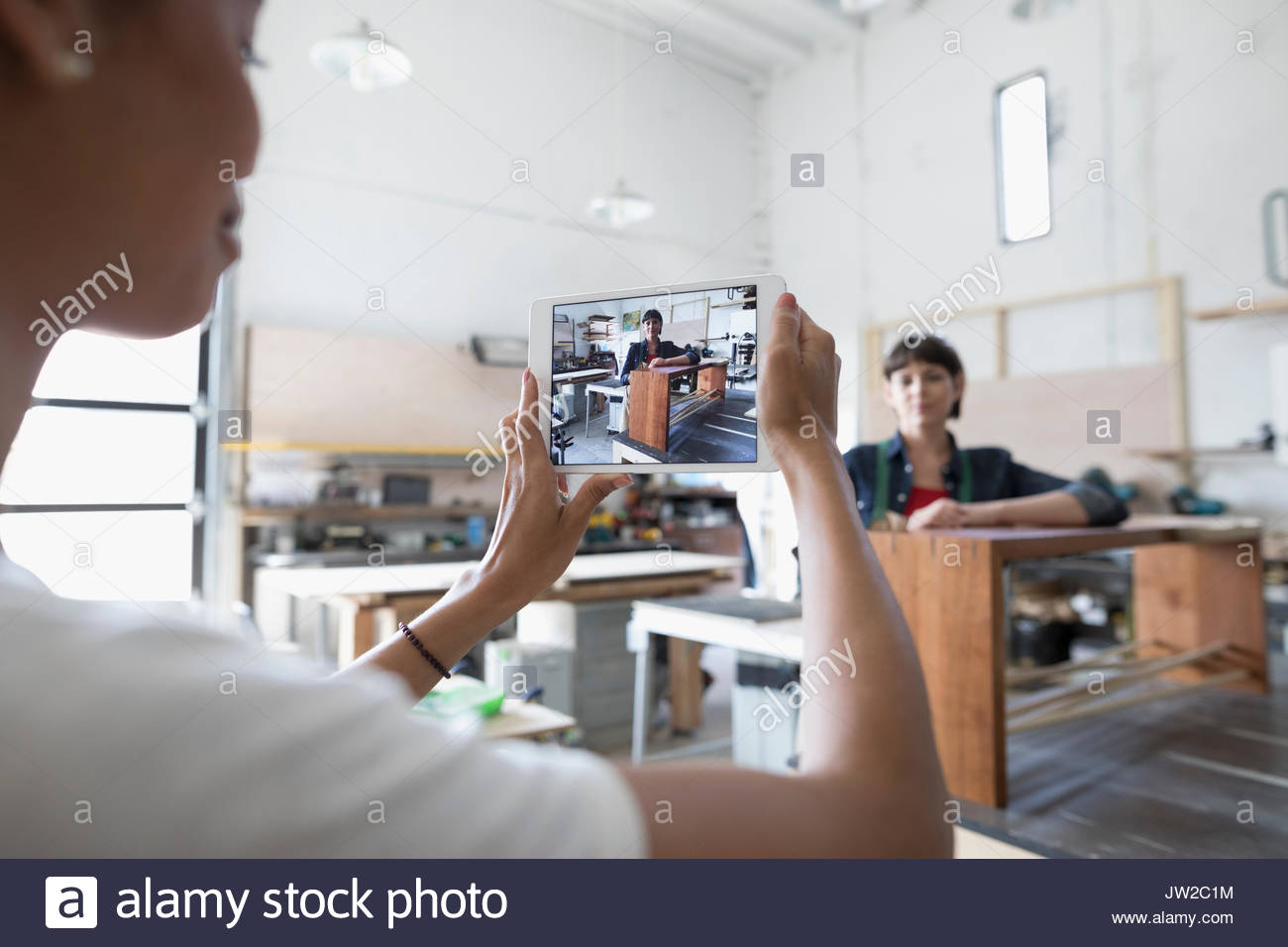 Female carpenter with digital tablet camera photographing coworker with wood bench in workshop - Stock Image