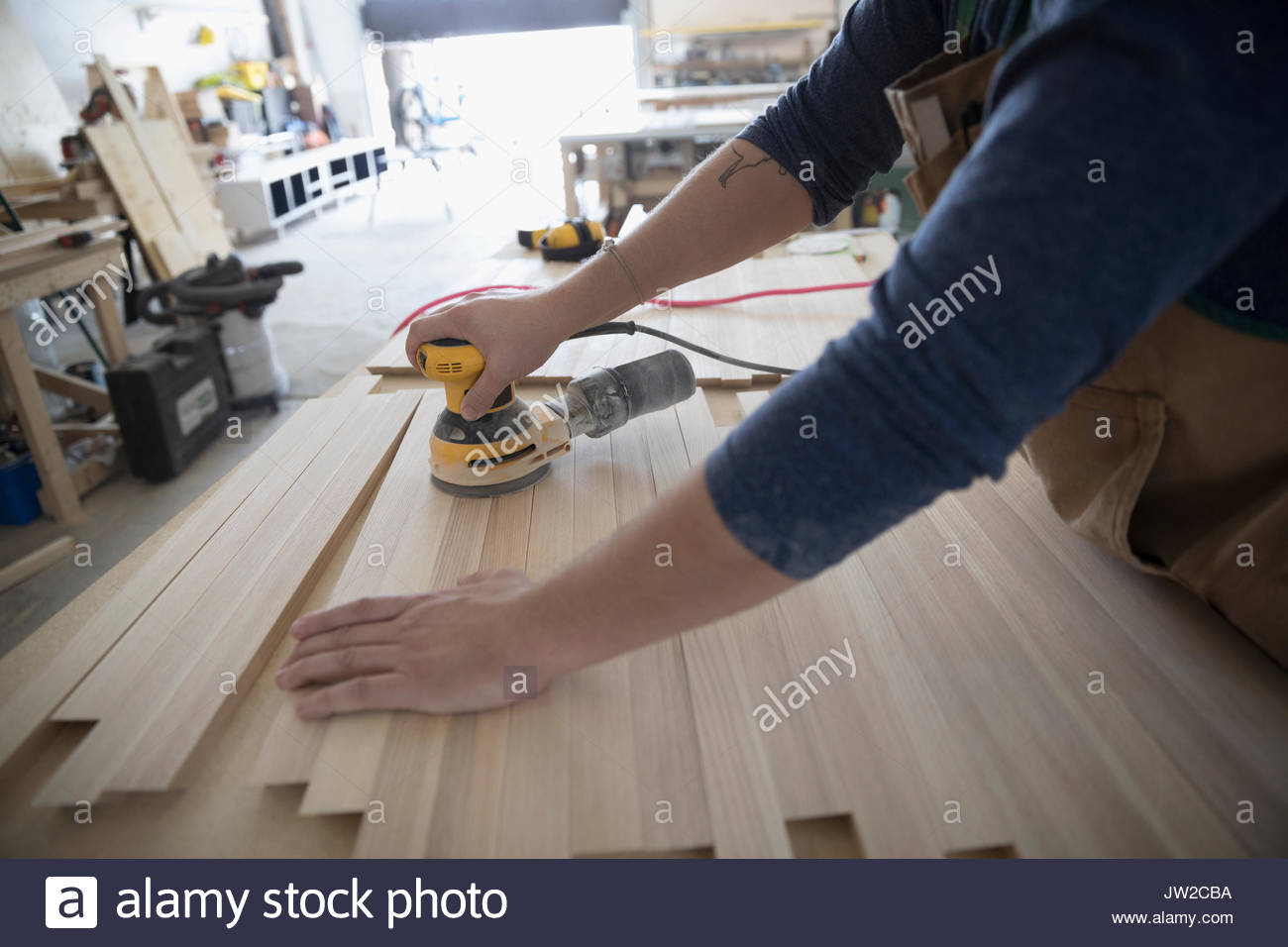 Male carpenter using sander to sand wood planks in workshop - Stock Image