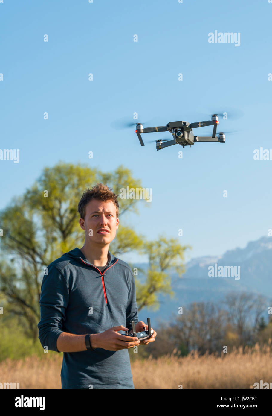 Young man controlling flying quadrocopter, remote controlled drone with camera, DJI Mavic - Stock Image