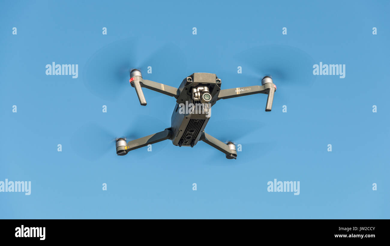 Flying quadrocopter, remote controlled drone with camera, DJI Mavic - Stock Image