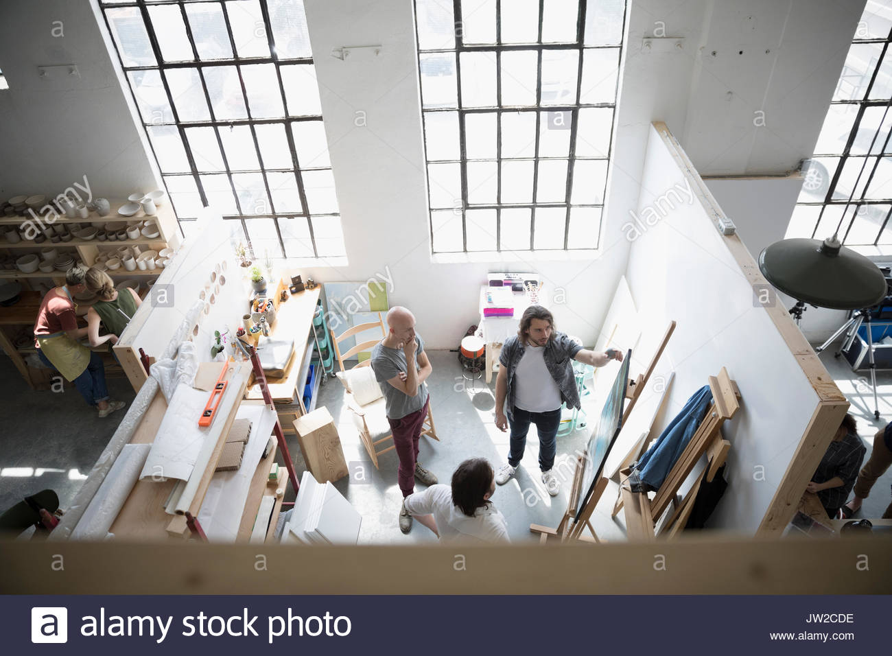 View from above painter students in painting class discussing canvas painting on easel in art studio - Stock Image