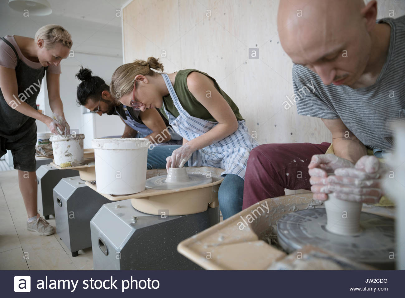 Pottery students learning how to use pottery wheels in art studio - Stock Image