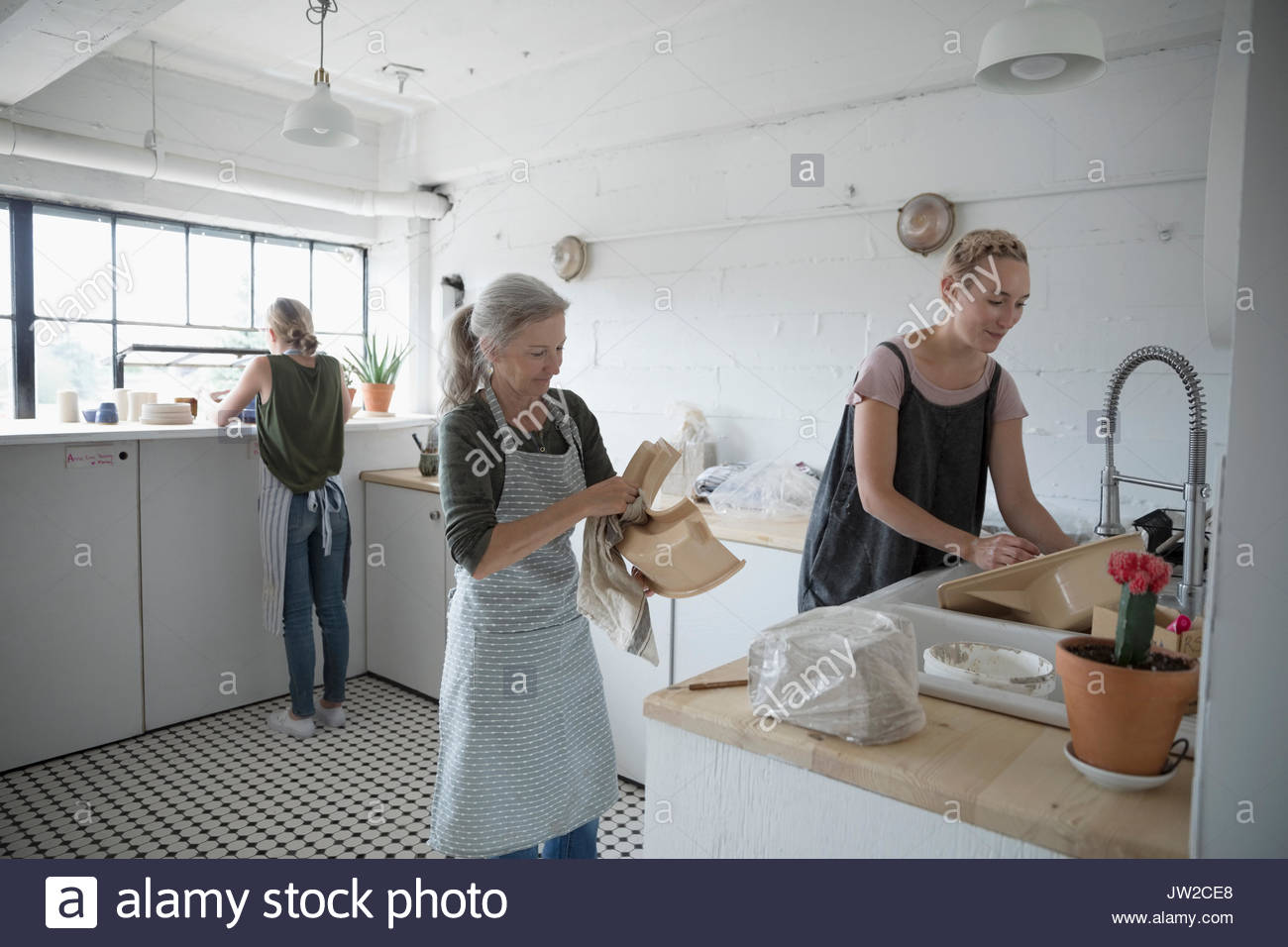 Female potters cleaning equipment in art studio - Stock Image