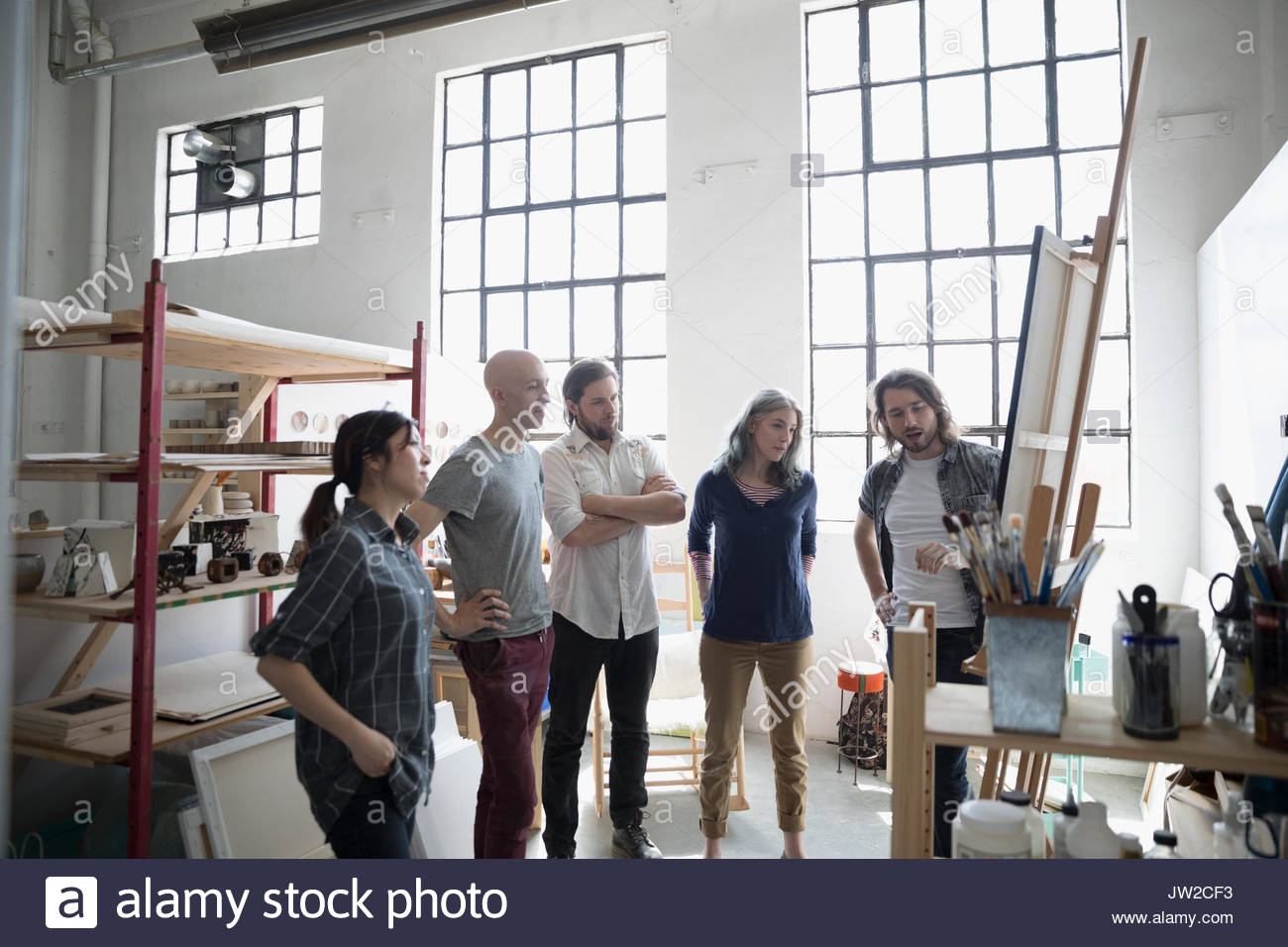 Painter students in painting class discussing canvas painting on easel in art studio - Stock Image