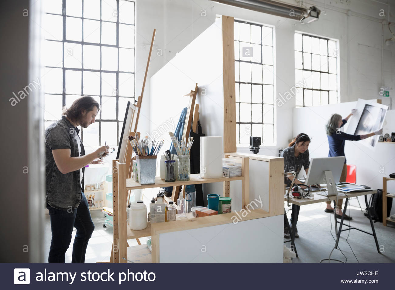 Painter painting at canvas on easel near photographers reviewing print in coworking space art studio - Stock Image