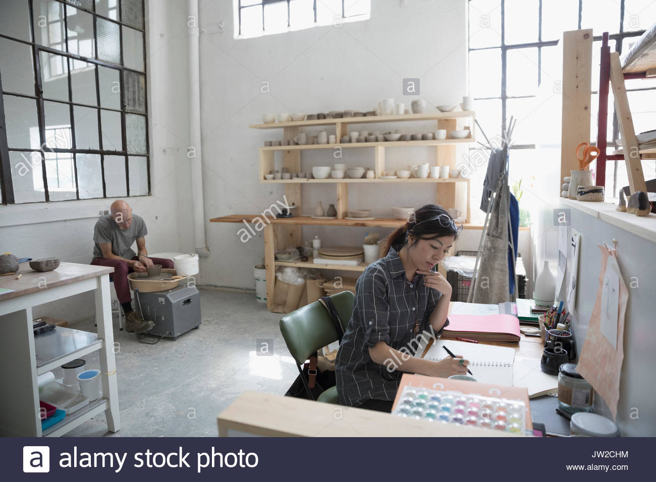 Artists sketching and using pottery wheel in art studio - Stock Image