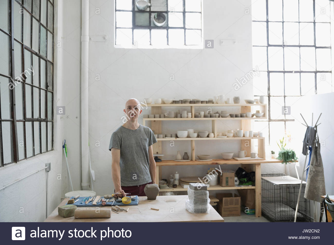 Portrait confident male potter sculpting at workbench in art studio ...
