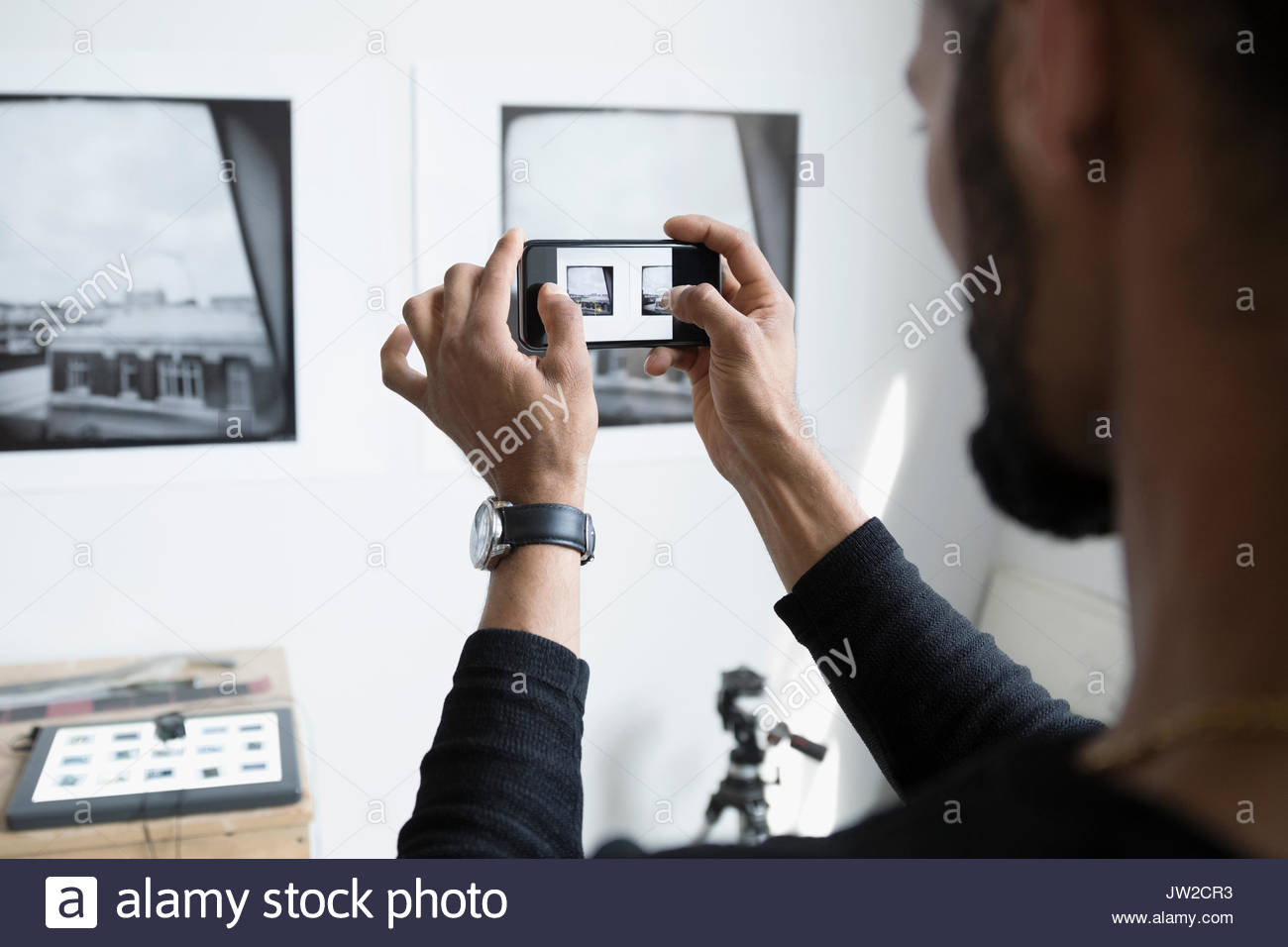 Male photographer with camera phone photographing prints on wall in art studio - Stock Image