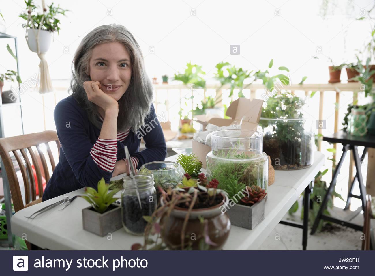 Portrait confident female shop owner making succulent plant terrariums - Stock Image