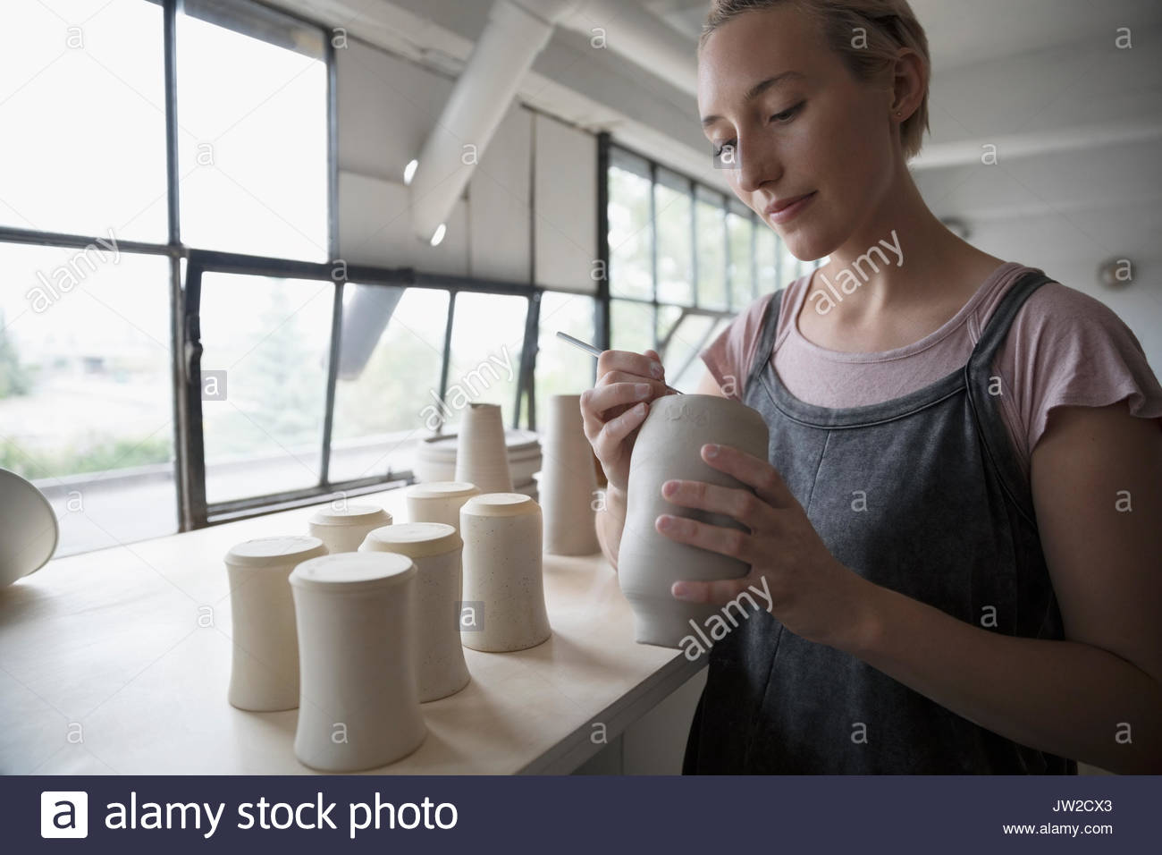 Female potter signing, marking bottoms of clay vases in pottery studio - Stock Image