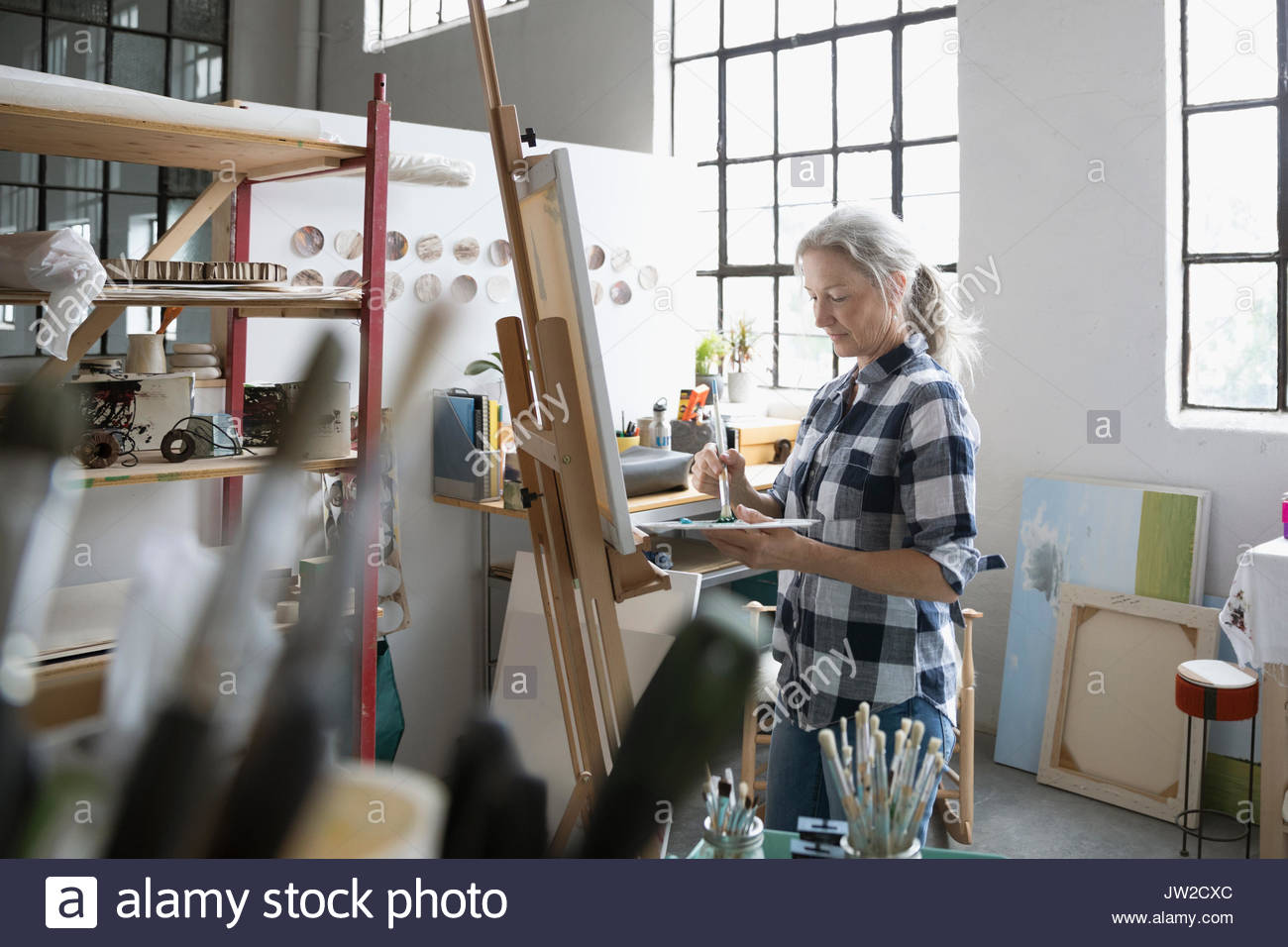 Female painter with palette painting at canvas in art studio - Stock Image