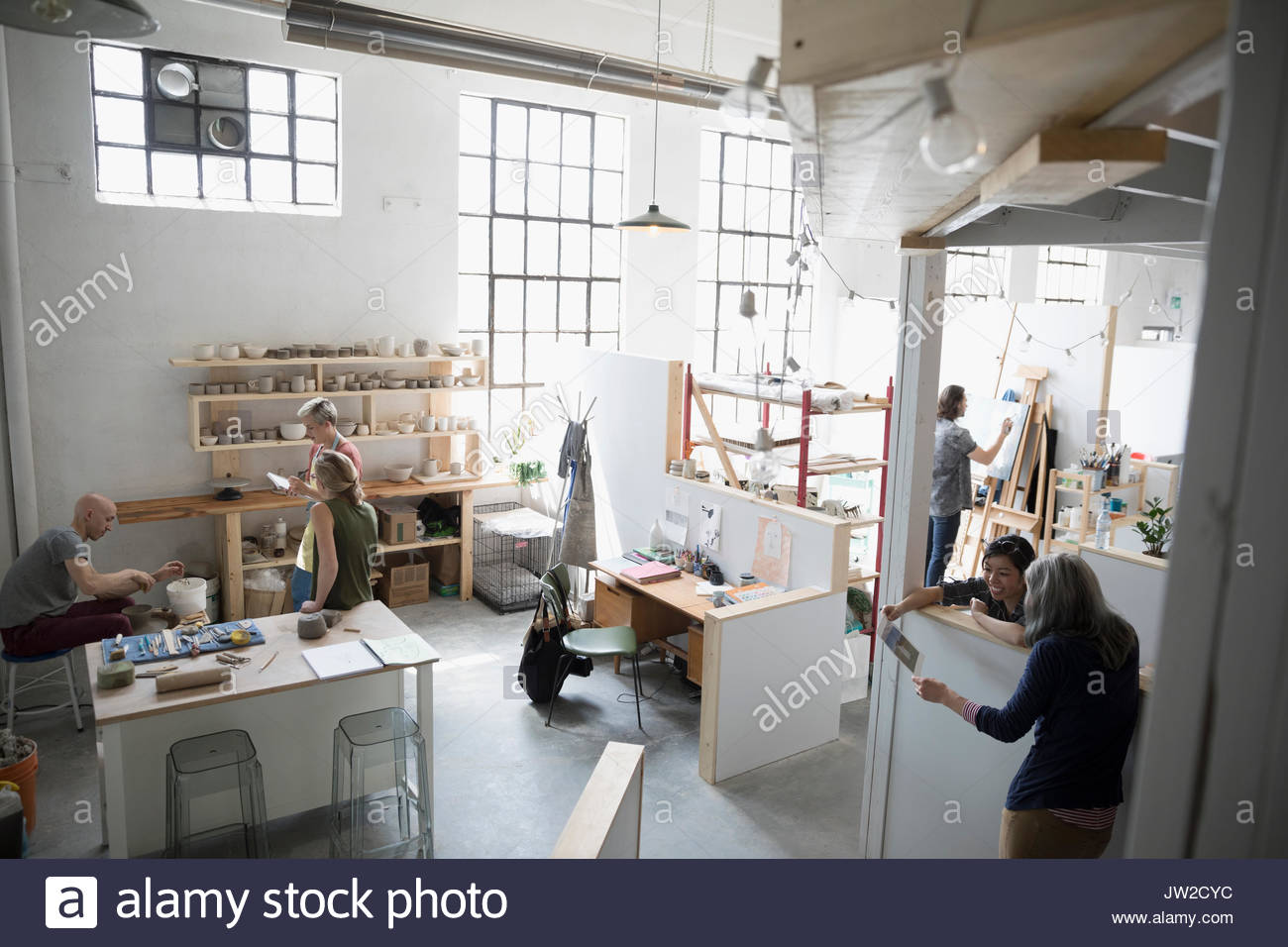 Artists painting, talking and using pottery wheel in coworking space art studio - Stock Image
