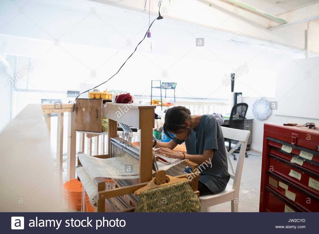 Female weaver weaving at loom in art studio Stock Photo