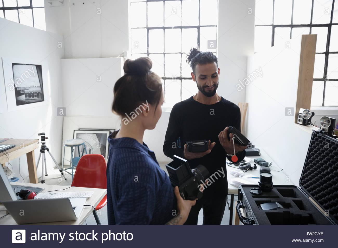 Photographers examining camera lens equipment in art studio - Stock Image